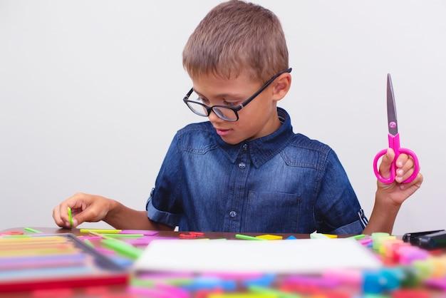 Scolaro in una camicia blu che si siede al tavolo. ragazzo con gli occhiali concetto torna a scuola Foto Premium