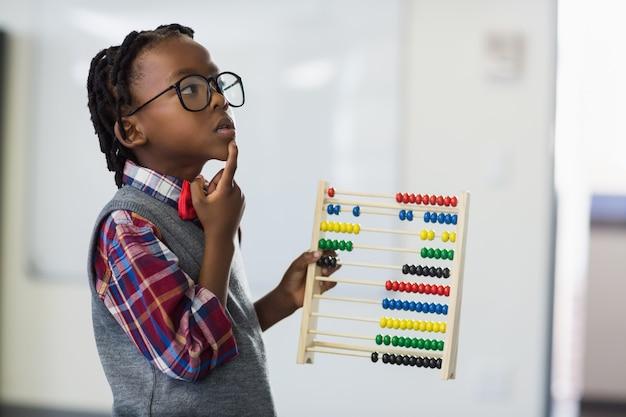 Scolaro premuroso che utilizza un abbaco di matematica nell'aula Foto Premium