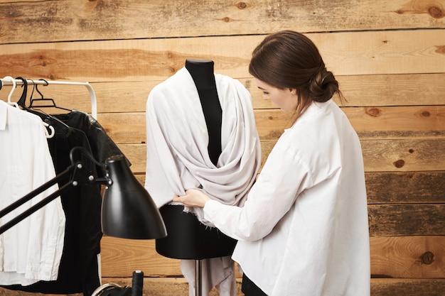 Scommetto che sarebbe bello sul modello. stilista di abiti di talento focalizzata che prova il suo capo sul manichino, preparandosi per la settimana della moda nel suo negozio di sartoria in legno. fogna creativa che pensa al nuovo concetto Foto Gratuite