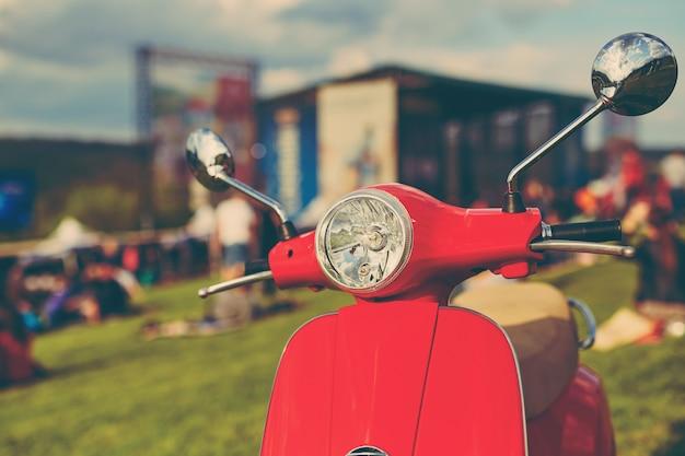 Scooter retrò rosso sull'erba Foto Gratuite