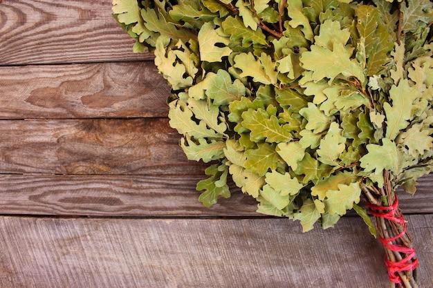 Scopa della quercia per un bagno su fondo di legno. Foto Premium