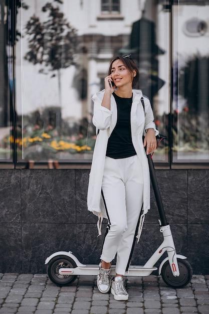 Scotter di guida della giovane donna in città e per mezzo del telefono Foto Gratuite