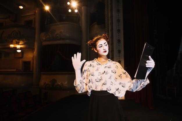 Script femminile della tenuta del mimo che prova sul palco Foto Gratuite