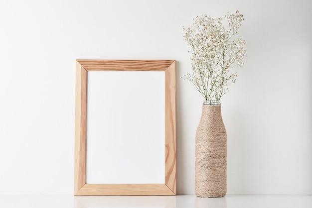 Scrittoio area di lavoro con cornice vuota e fiore in vaso Foto Premium
