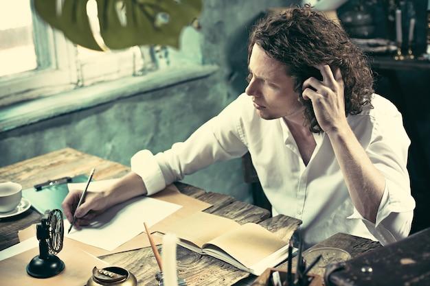 Scrittore al lavoro. bel giovane scrittore seduto al tavolo e scrivere qualcosa nel suo blocco per schizzi Foto Gratuite