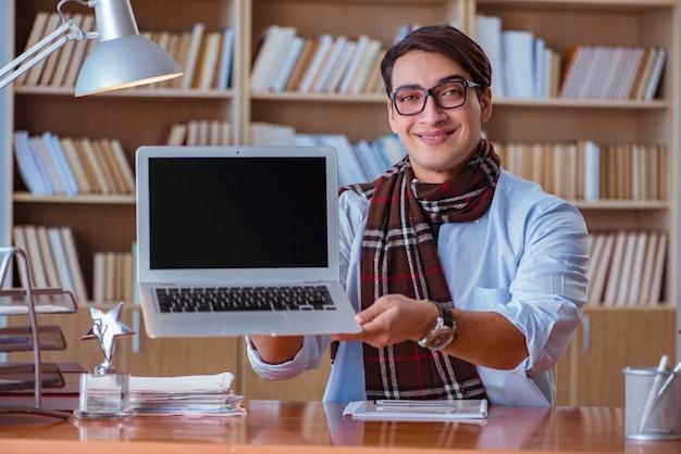 Scrittore giovane che scrive in biblioteca Foto Premium