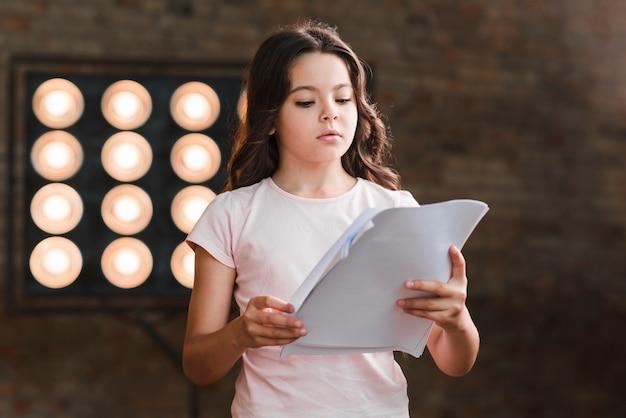 Scrittorio della lettura della ragazza che sta contro la luce della fase Foto Gratuite
