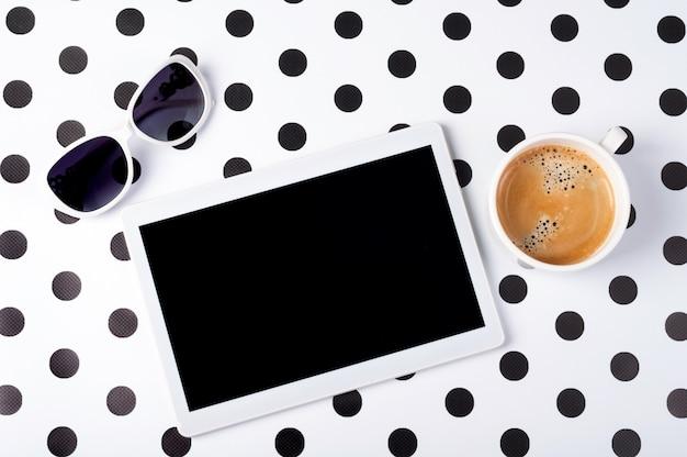 Scrittorio femminile con la compressa, tazza di caffè, occhiali da sole sulla vista superiore del fondo creativo Foto Premium