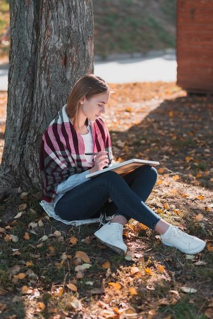 Scrittura bionda della ragazza in un taccuino Foto Gratuite