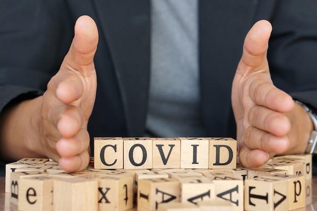 Scrittura covid-19 in pezzi di lettere di legno simili a quelle di un gioco di scrabble Foto Premium