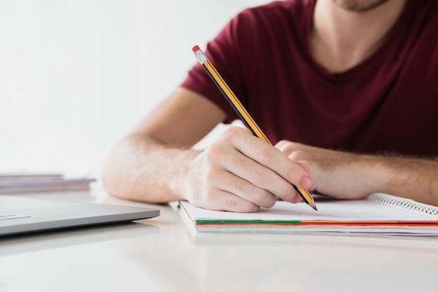 Scrittura dell'uomo sul suo blocco note con la matita Foto Gratuite