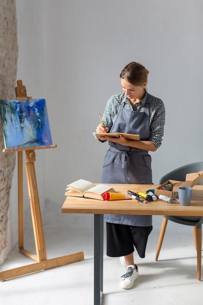 Scrittura della donna in taccuino in studio Foto Gratuite