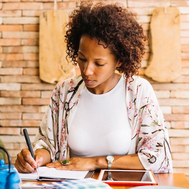Scrittura della giovane donna in diario con la penna e la compressa digitale sulla tavola di legno Foto Gratuite