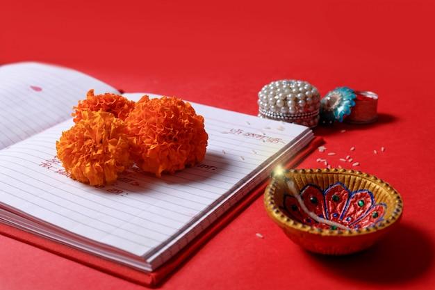 Scrittura di calligrafia in hindi shubha labh significa bontà e ricchezza, sul quaderno rosso di contabilità, diya, Foto Premium