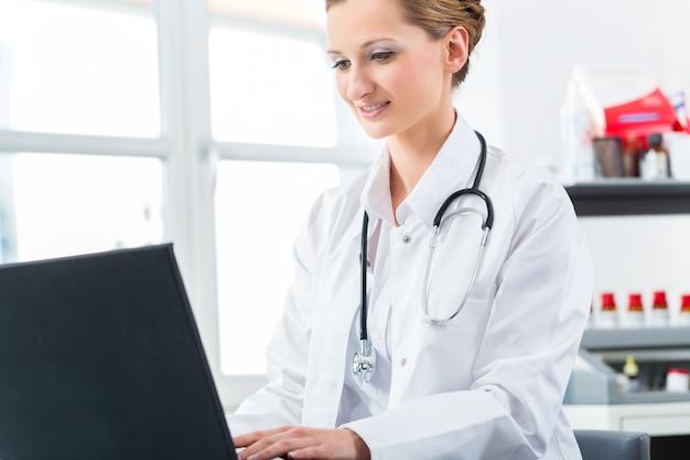 Scrittura femminile del medico sul pc nella sua clinica Foto Premium