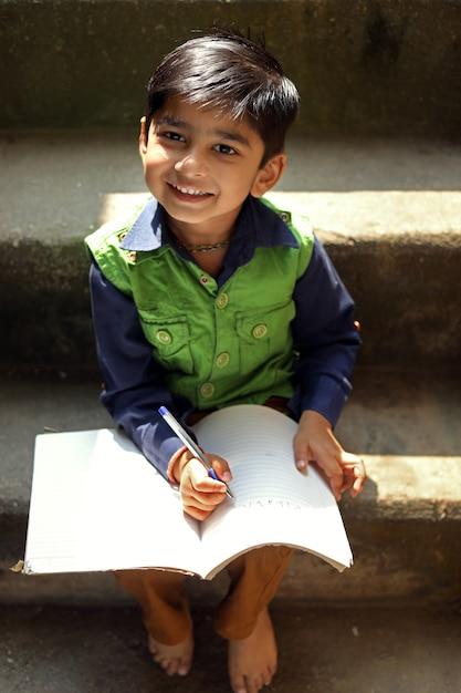 Scrittura indiana del bambino sul taccuino Foto Premium