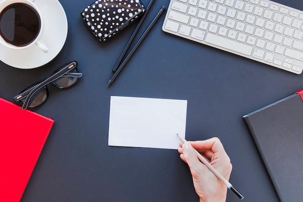 Scrittura senza volto della persona sulla nota vicino a cancelleria e tastiera sullo scrittorio con la tazza di caffè Foto Gratuite