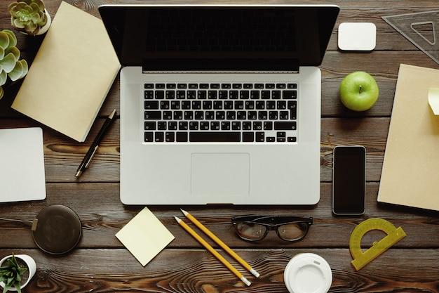Scrivania con computer portatile, forniture e mela verde, vista dall'alto Foto Premium