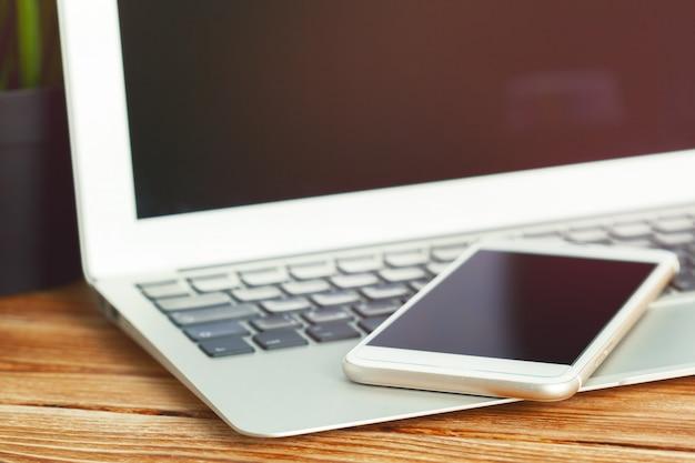 Scrivania con lo smart phone del computer portatile e il fondo dell'ufficio di affari. Foto Premium