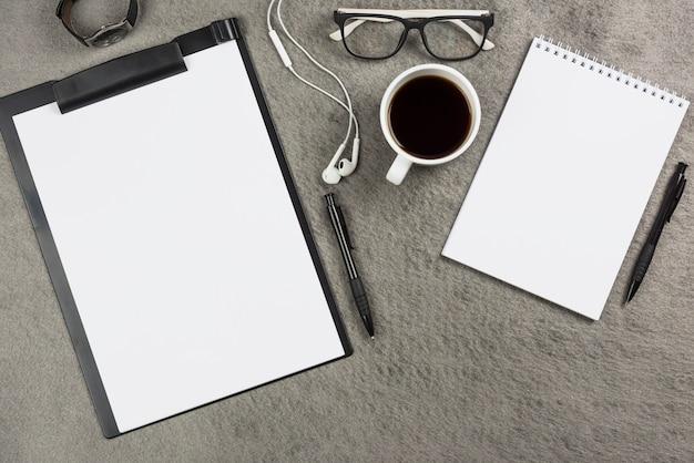 Scrivania da ufficio grigia con tazza di caffè; auricolari e occhiali Foto Gratuite