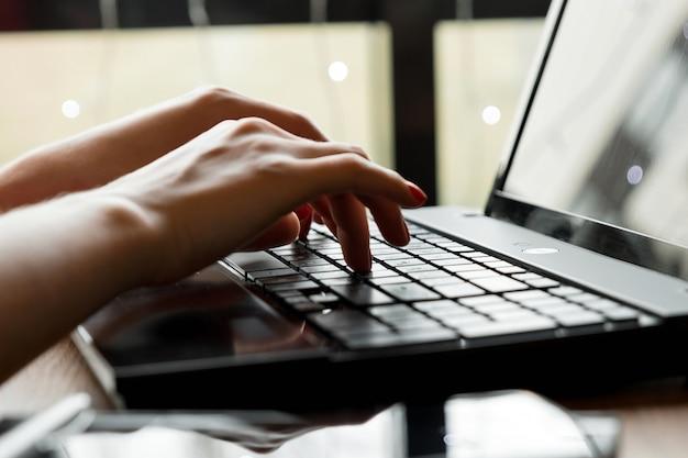 Scrivania del primo piano. area di lavoro con le mani della ragazza, laptop, tazza di caffè. donna d'affari. Foto Premium