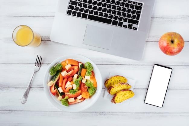 Scrivania e computer portatile con cibo sano Foto Gratuite