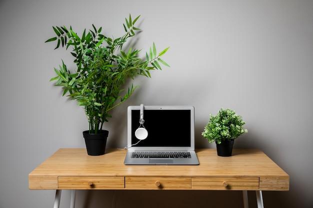 Scrivania in legno con laptop e cuffie grigie Foto Gratuite