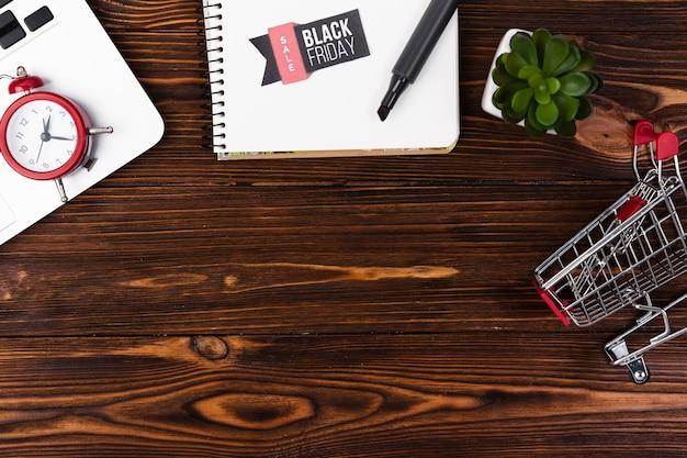 Scrivania in legno vista dall'alto con adesivo venerdì nero sul blocco note Foto Gratuite