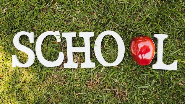 Scuola di parole bianche con apple su erba Foto Gratuite
