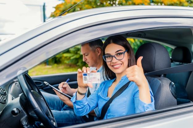 Scuola guida. la bella giovane donna ha passato con successo la prova di scuola guida. lei sta guardando Foto Premium
