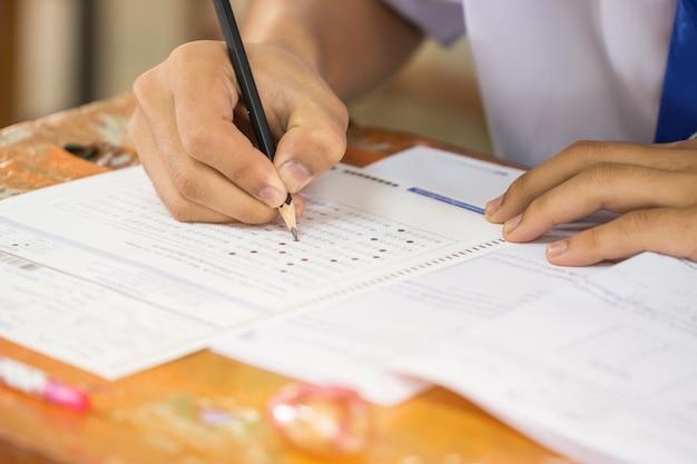 Scuola / università le mani degli studenti che sostengono gli esami, scrivendo la stanza dell'esame con la matita di tenuta sulla forma ottica, rispondono allo strato di carta sulla scrivania facendo il test finale in aula. concetto di valutazione dell'istruzione Foto Premium
