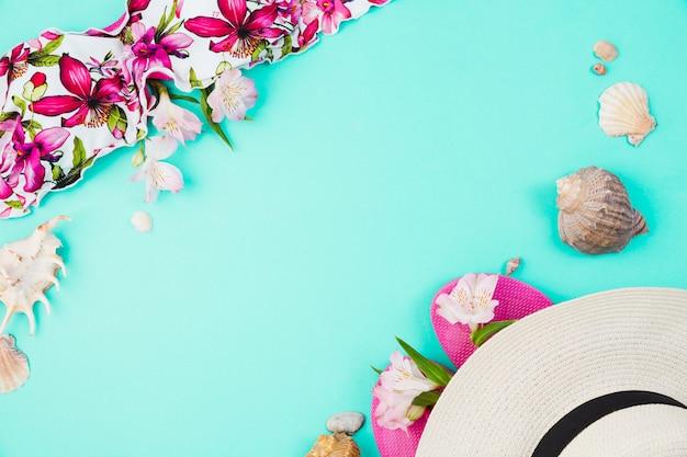 Seashells e costume da bagno vicino a infradito con cappello Foto Gratuite