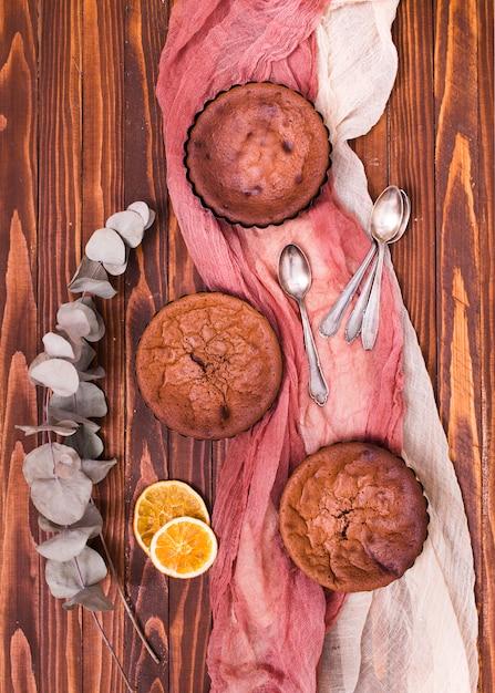 Secchi foglie di eucalipto populus e fette di agrumi con tre torte e cucchiai su vestiti di lino sopra il tavolo di legno Foto Gratuite