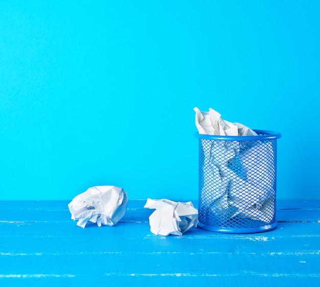 Secchio di metallo blu pieno di carta bianca stropicciata Foto Premium