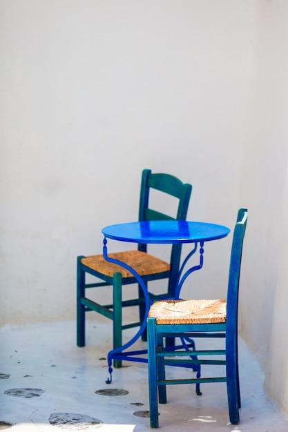 Sedia e tavola blu sulla via del villaggio tradizionale greco tipico sull'isola di mykonos, grecia, europa Foto Premium