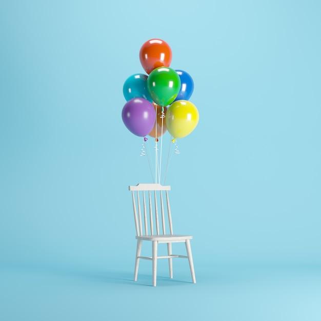 Sedia in legno con palloncini colorati che galleggiano su sfondo blu. Foto Premium