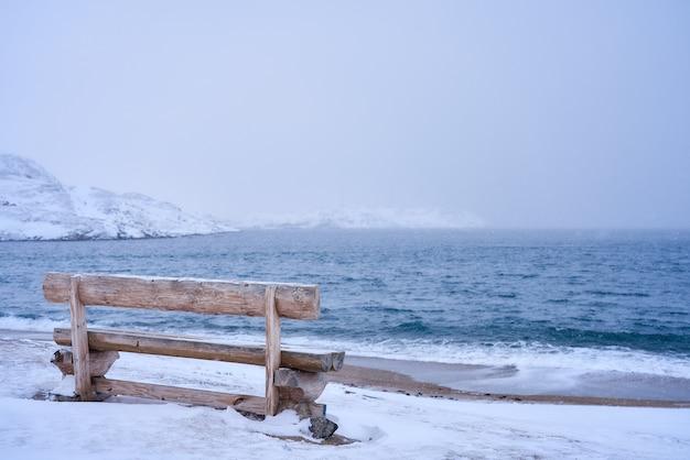 Sedia in legno, tempo di relax a teriberka con il mare di barents nella parte più settentrionale del mondo Foto Premium