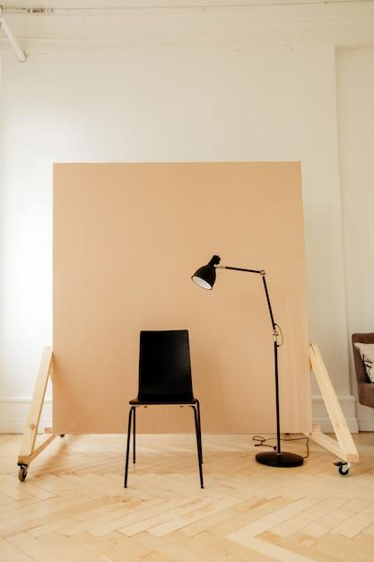Sedia nera con lampada in camera per sessione fotografica Foto Premium