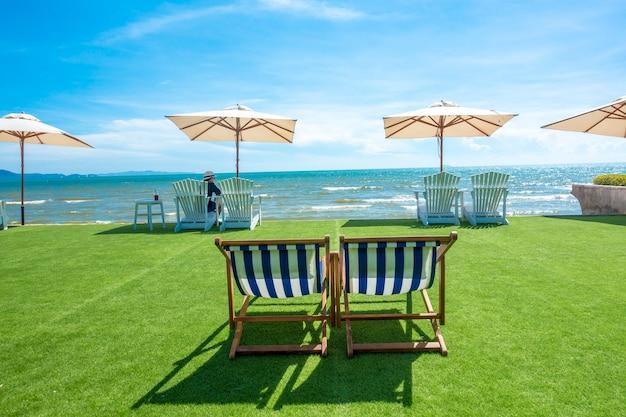 Sedie a sdraio con ombrellone su una spiaggia Foto Premium