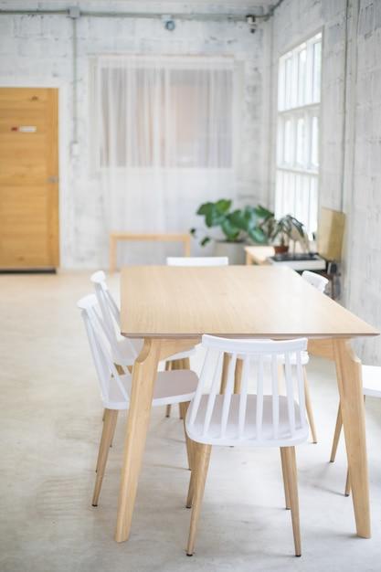 Sedie bianche e tavola di legno alla stanza Foto Premium