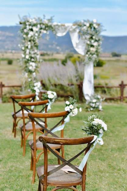 Sedie chiavari marroni decorate con mazzi di eustomas bianchi sull'erba e l'arco di nozze decorato sullo sfondo il giorno soleggiato Foto Gratuite