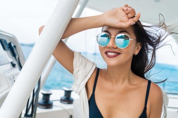 Seduta e guida castana attraenti e splendide di una barca a motore moderna. ragazza adorabile che si rilassa e che posa per la macchina fotografica. modella indossa bikini nero. vacanze estive di lusso Foto Premium