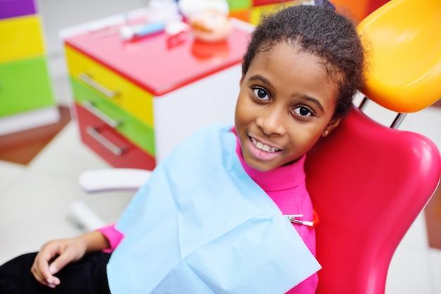 Seduta sorridente della neonata nera sveglia in una sedia dentaria rossa Foto Premium