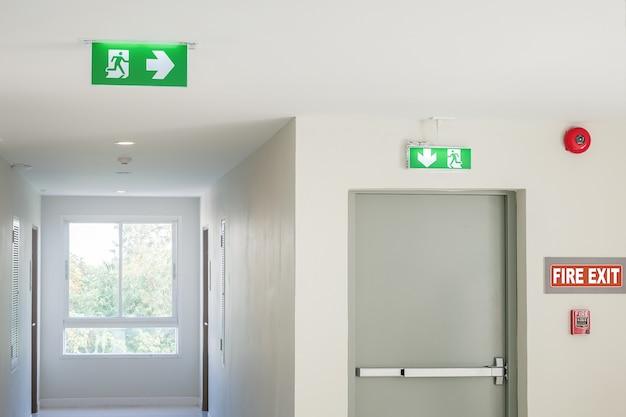 Segnale di uscita antincendio con luce sul percorso del percorso in hotel o in ufficio Foto Premium