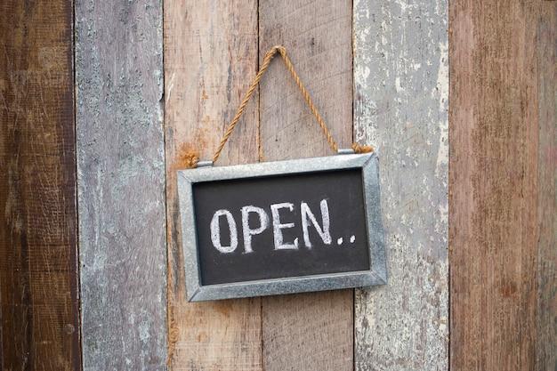 Segno aperto sulla porta del negozio in legno Foto Premium