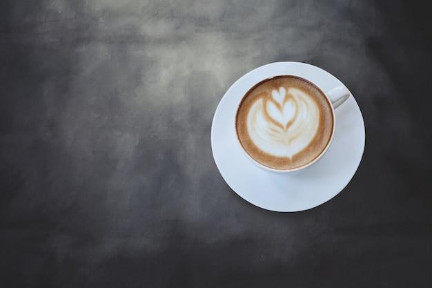 Segno del cuore sul caffè di arte del latte sul fondo nero di colore. Foto Premium