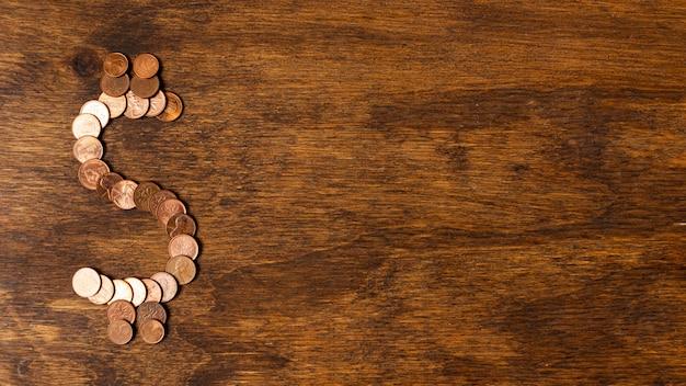 Segno del dollaro fatto dalle monete sul fondo di legno dello spazio della copia Foto Gratuite