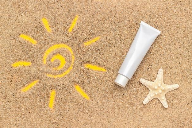 Segno del sole disegnato sulla sabbia, stella marina e tubo bianco di crema solare. Foto Premium
