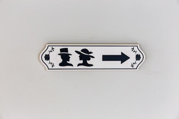 Segno dell'icona dei bagni di legno con il simbolo maschio e femminile e la freccia di direzione Foto Premium