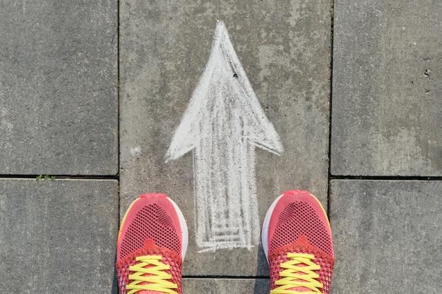 Segno della freccia dipinto sul marciapiede grigio con le gambe delle donne in scarpe da tennis Foto Premium